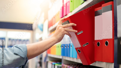Photo Male hand choosing new red ring binder file folder from colorful shelf display in stationery shop