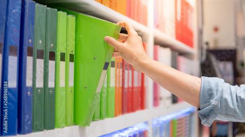 Fototapeta Male hand choosing new green ring binder file folder from colorful shelf display in stationery shop