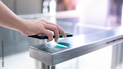 Cuadros en Lienzo Male hand using smartphone to open automatic gate machine in office building
