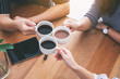 Close up image of three people enjoyed drinking and clinking coffee cups on wooden table in cafe