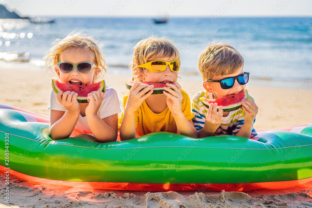 Fototapeta Children eat watermelon on the beach in sunglasses