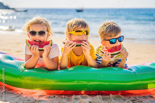 Dzieci jedzą arbuza na plaży w okularach przeciwsłonecznych