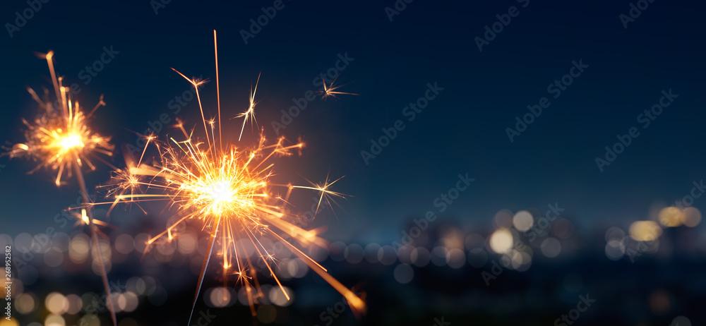 Fototapety, obrazy: Burning sparkler with blurred bokeh cities light background