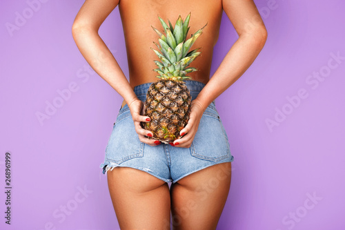 Fotografie, Obraz  Young woman holding a pineapple in her hand on purple background