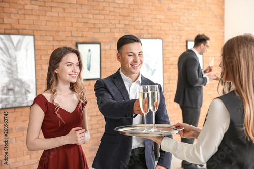 Fotografía  Waiter suggesting champagne to visitors of modern art gallery