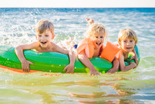 Children Swim In The Sea On An Inflatable Mattress And Have Fun