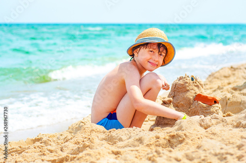 Fototapeta A happy boy is building a sand castle on the shore of a turquoise sea on a sunny day. Children's and family rest on the sea in the summer. obraz na płótnie