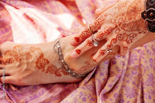 Photo Female hand and leg decorated with traditional Indian henna