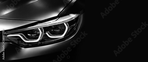 Detail on one of the LED headlights modern car on black background - 268972119