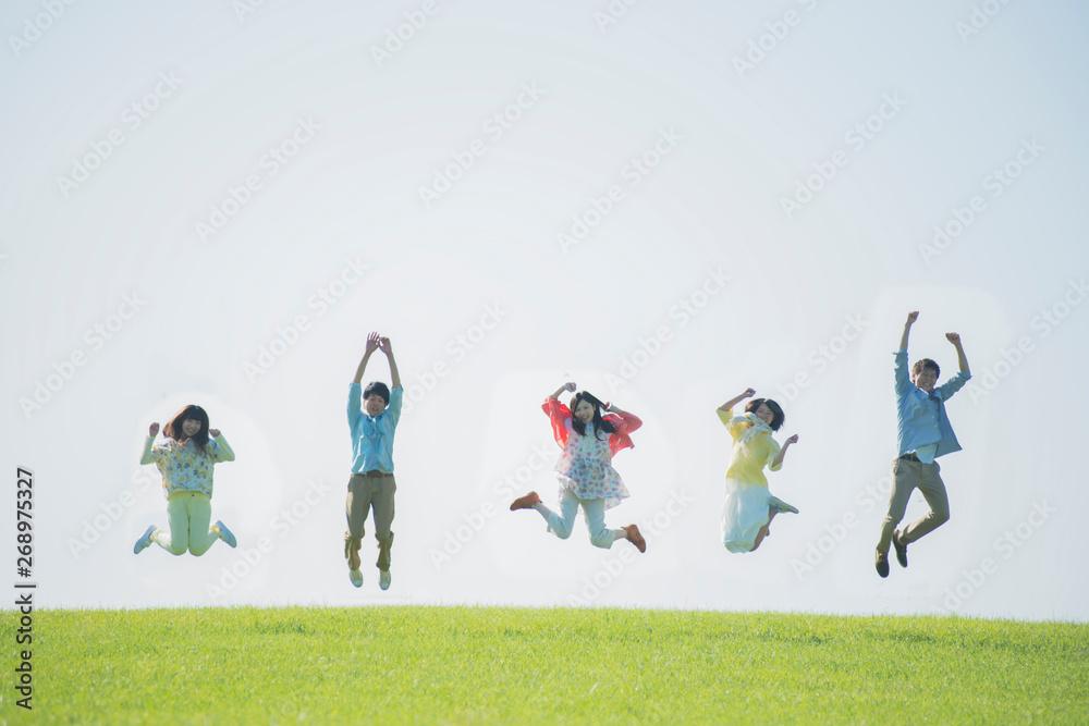 Fototapeta 草原でジャンプをする大学生