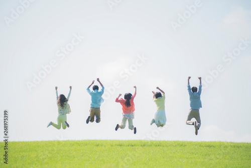 Obraz 草原でジャンプをする大学生の後姿 - fototapety do salonu
