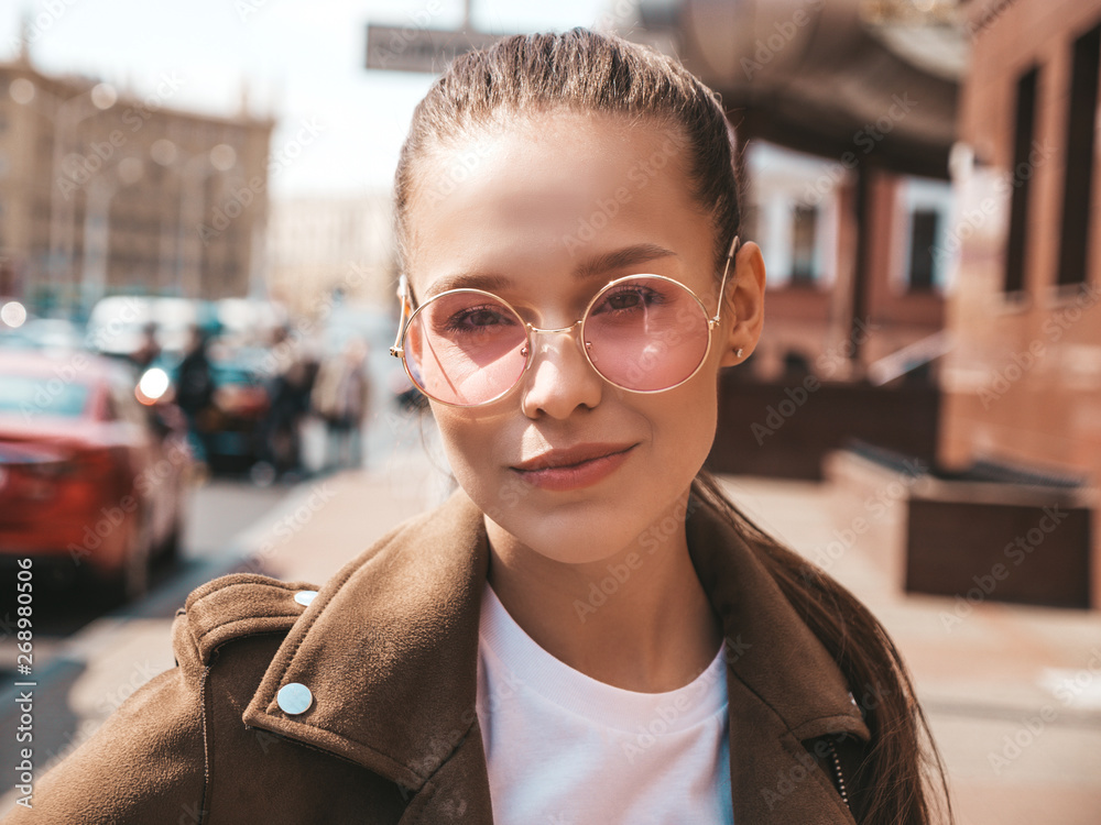 Fototapety, obrazy: Portrait of beautiful brunette model dressed in summer hipster jacket clothes. Trendy girl posing in the street background. Funny and positive woman in round sunglasses