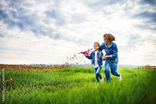 Fotografie, Obraz  Young woman and girl in denim clothes having fun with small plane on green lawn