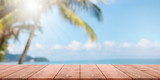 Fototapeta Fototapety z morzem do Twojej sypialni - Empty wood table top and blurred summer beach with blue sea and sky banner background. - can used for display or montage your products.