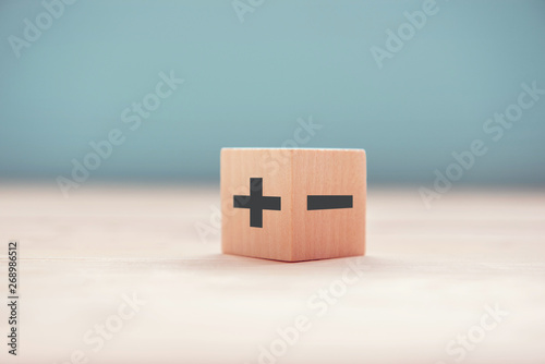 The concept of opposites, wood blog with plus and minus on blue background, flat lay, copy space Wallpaper Mural