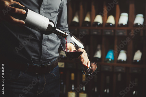 Foto Close up shot of sommelier pouring red wine from bottle in glass on underground