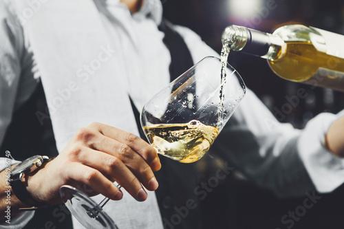 Fotografía  Male sommelier pouring white wine into wineglasses.