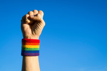 Gay Protestor Punching The Air In Defiance With Gay Pride Rainbow Colors Wristband Against Bright Blue Sky