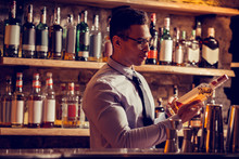 Businessman Wearing Tie Looking At Bottle Of Whisky In His Restaurant