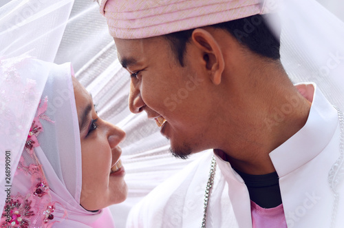 Fotomural close up portrait of a malay bride and groom under veil with lovely emotion