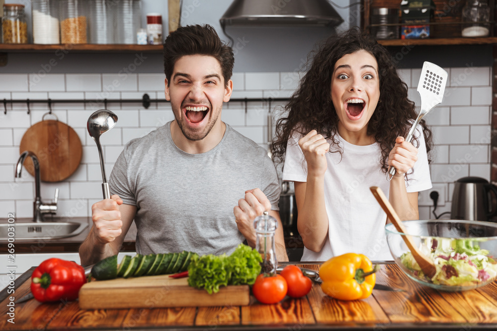 Fototapety, obrazy: Excited cheerful young couple cooking healthy salad