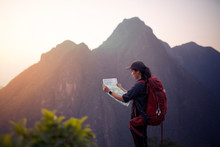 Backpacker Woman Standing On Top Of Mountain And Looking Map With Nature Background