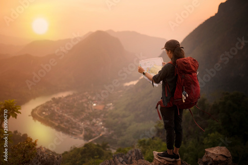 Backpacker woman standing on top of mountain and looking map with nature backgro Wallpaper Mural