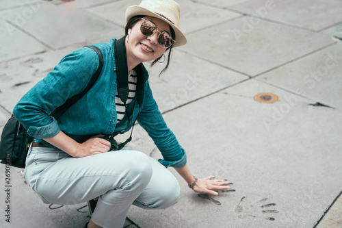 Photo  smiling asian woman traveler face camera looking joyful puts hand in handprint of famous star in chinese theater in hollywood los angeles california USA