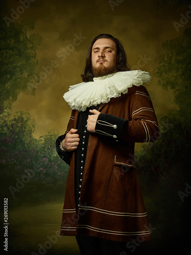 Obraz na plátně Young man as a medieval knight on dark studio background