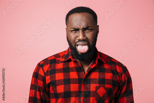 Fotografie, Tablou  Portrait of a disgusted african man wearing plaid shirt