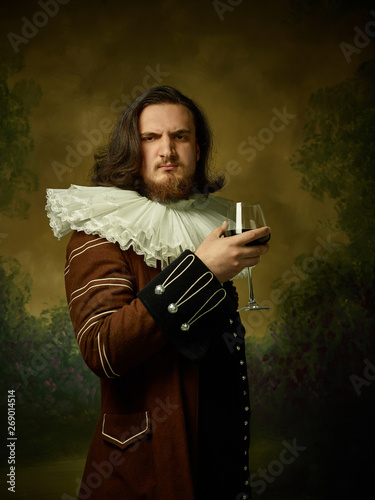 Young man as a medieval knight on dark studio background Wallpaper Mural