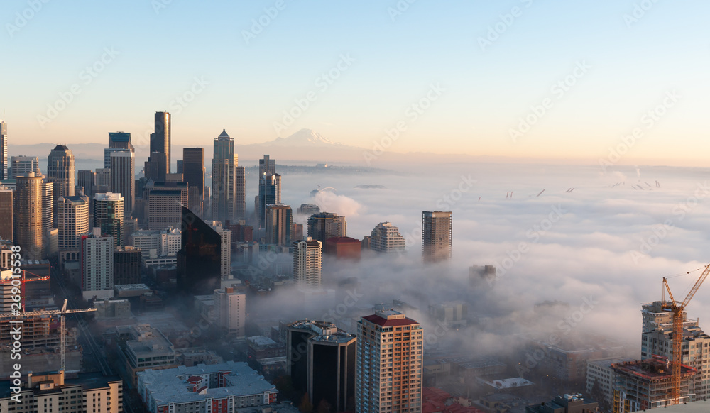 Fototapety, obrazy: Partially immersed in the fog from Elliott Bay, this panoramic view of Seattle at sunset,in a cold autumn day, with blue sky and the Mount Rainier visible on the background.