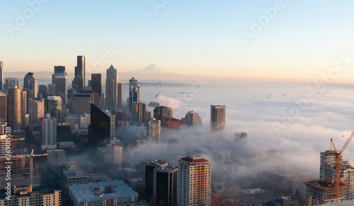 Partially immersed in the fog from Elliott Bay, this panoramic view of Seattle at sunset,in a cold autumn day, with blue sky and the Mount Rainier visible on the background фототапет
