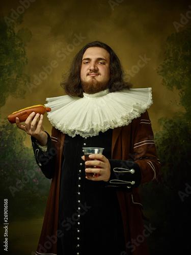 Obraz na plátne Young man as a medieval knight on dark studio background