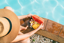 Caucasian Woman In Straw Hat Sitting On Swimming Pool Side Near Plate Of Tropical Fruits- Camera And Trying To Eat Watermelon. Top View Oimage.