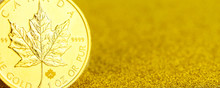 Silver And Golden Canadian Maple Leaf One Ounce Coins On Golden Background