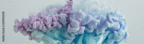 Obraz Close up view of light blue, pink and purple paint swirls in water - fototapety do salonu