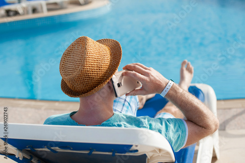 Fototapeta man lying on a lounger and talking on a phone near the pool