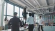 Employees celebrate the end of the work week, have fun dancing on the table. Managers enjoy success and victory. Corporate party business team. Coworking. Modern trendy office interior