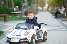 Cute Little Boy Driving Mechanical Toy Car Turning The Steering Wheel With A Look Of Concentration As He Plays In A City Park