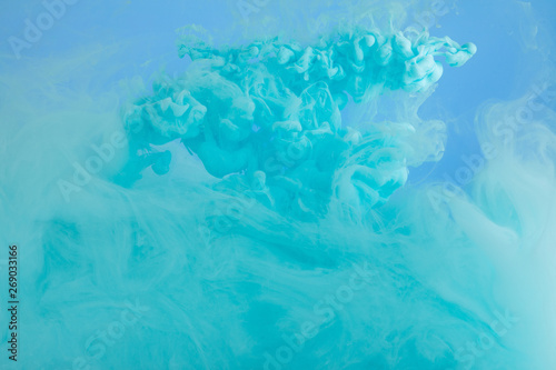 Stickers pour porte Eau Close up view of turquoise watercolor paint swirls isolated on blue