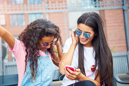 Poster Magasin de musique Girlfriends sitting outside listening and singing to music on earphones