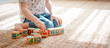 Leinwandbild Motiv child plays with wooden blocks with letters on the floor in the room a little girl is building a tower at home or in the kindergarten.