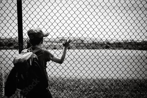 Foto Kind schaut durch Zaun