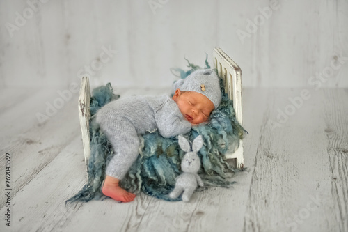 Obraz A newborn baby boy is sleeping on a little cot in the first days of life  - fototapety do salonu