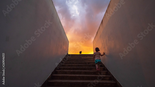 Children are walking up the stairs  at sky sunset