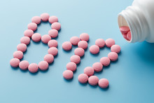 Pink Round Vitamins B12 Shaped Pills On A Blue Background Spilled From A White Can