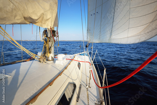 Fototapeta White yacht sailing on a clear sunny day. Close-up view from the deck to the bow and sails. Waves and water splashes. Brittany, France obraz na płótnie