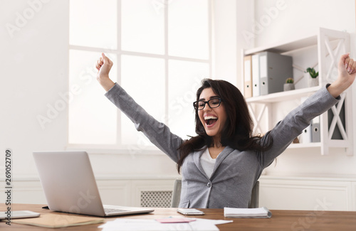 Fotografía  Excited Businesswoman Celebrating Success With Raised Hands At Workplace