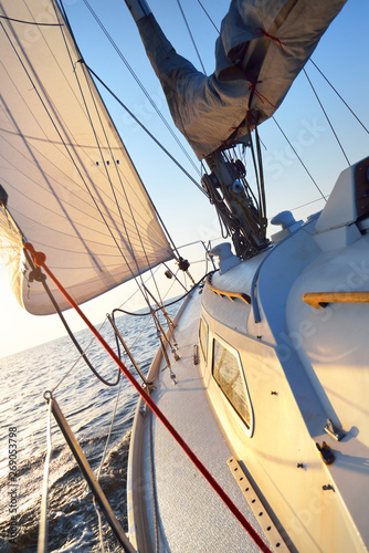 Fototapety, obrazy: White yacht sailing on a clear sunny day. Close-up view from the deck to the bow and sails. Waves and water splashes. Brittany, France